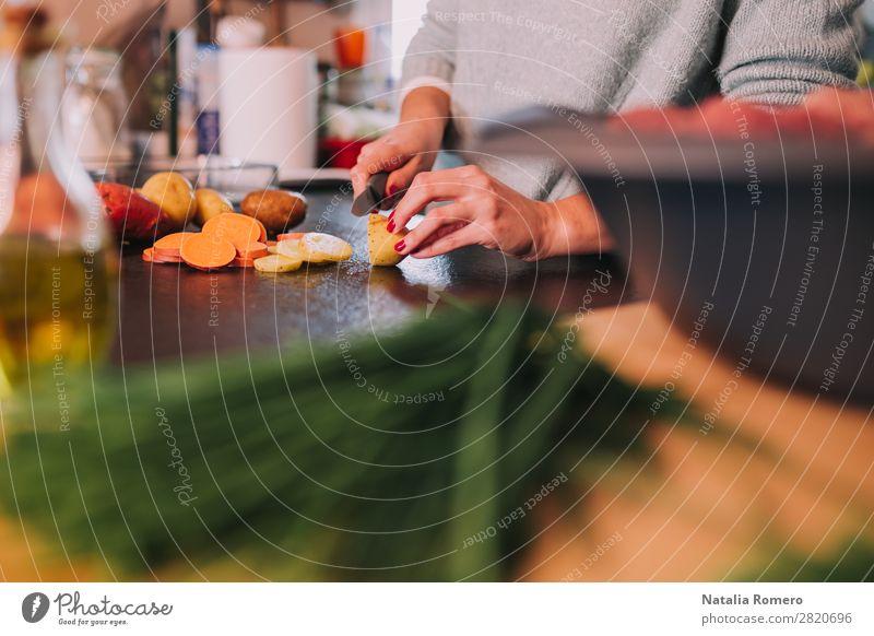 eine Person, die Kartoffeln und Süßkartoffeln in einer schönen Küche schneidet. Gemüse Essen Mittagessen Abendessen Diät Tisch Mensch Frau Erwachsene Hand Natur