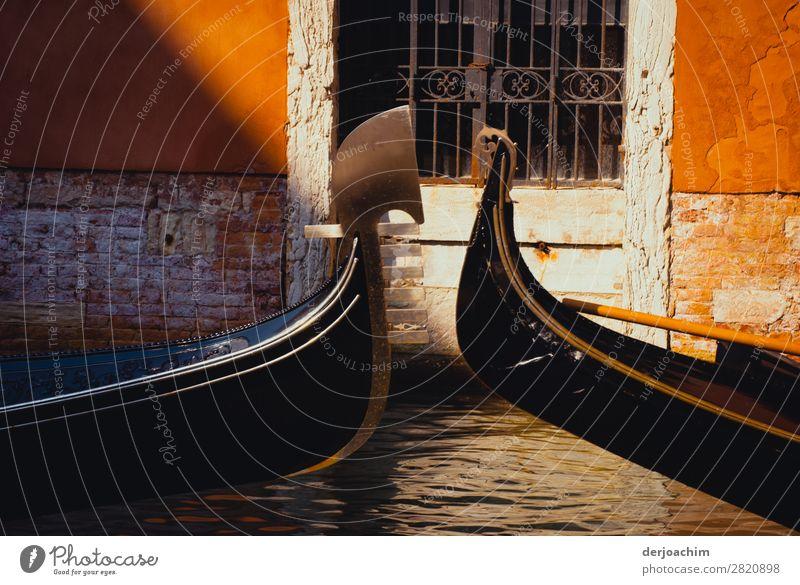 Begegnung von  zwei Gondeln die sich begegnen  in den Kanälen..von Venedig. Man sieht nur die Vorderseite der Boote. Im Hintergrund eine Alte Tür mit Gitter.