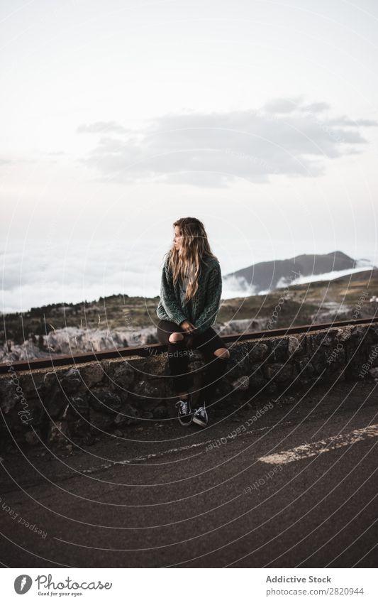 Frau am Straßenrand sitzend Zaun Berge u. Gebirge Nebel Wolken Jugendliche