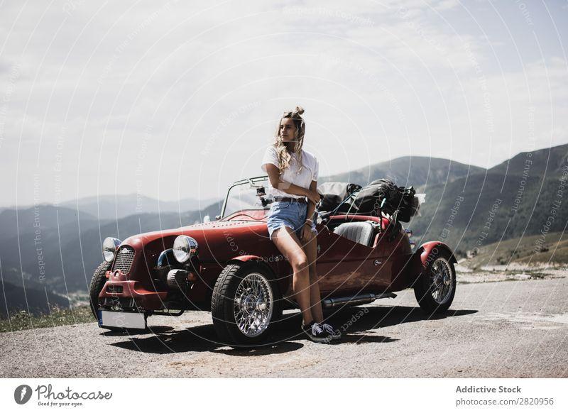 Frau steht am Oldtimer. PKW altehrwürdig Straße rot anlehnen Motorhaube stehen Berge u. Gebirge Mädchen Jugendliche Laufwerk Fahrzeug Lifestyle Sommer schön