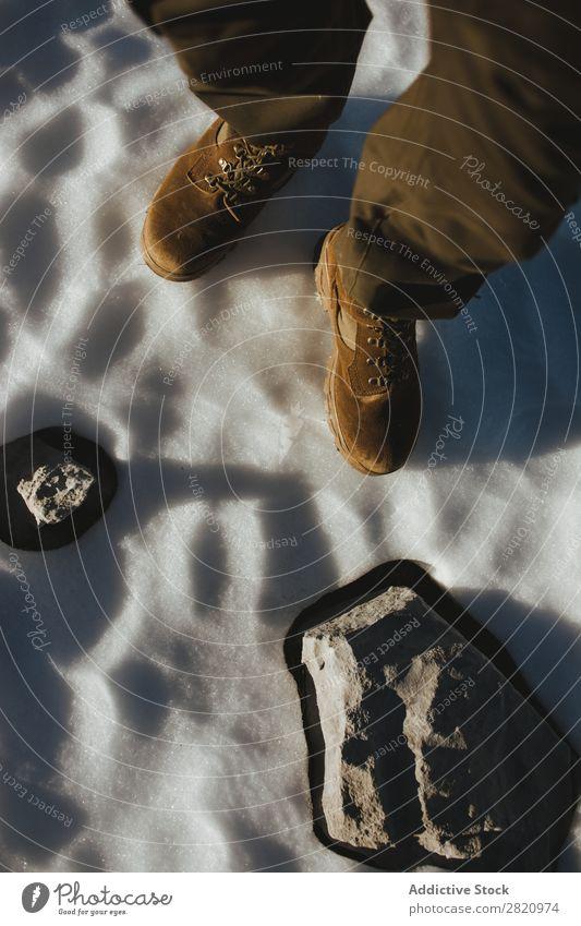 Person auf Schnee mit Felsen kultivieren Mann Stiefel stehen Stein Winter natürlich lässig kalt Wetter Schuhe Beine Frost Sonnenlicht frisch Natur Fuß weiß