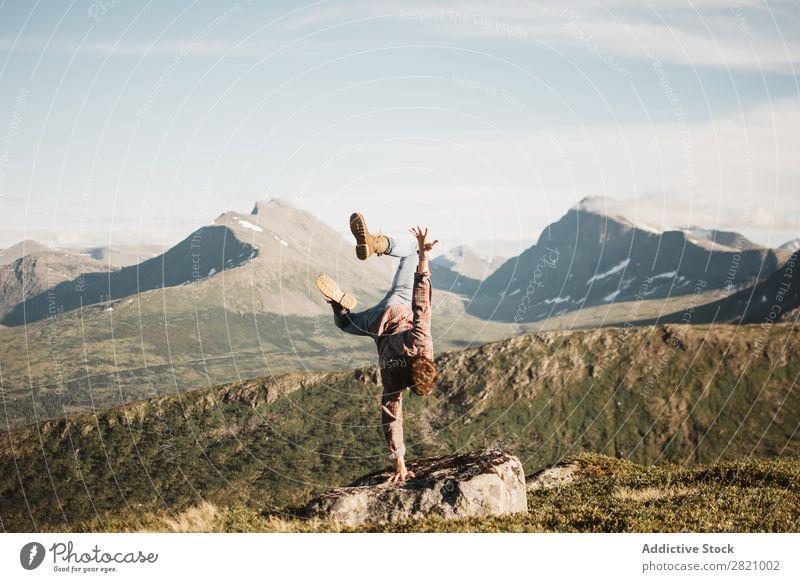 Mann, der in der Landschaft auf der Hand steht. Handstand Natur Berge u. Gebirge extrem Gleichgewicht Panorama (Bildformat)