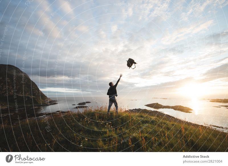 Mann wirft Rucksack auf die Landschaft Werfen Freiheit Ferien & Urlaub & Reisen Natur Außenaufnahme spielerisch Küste friedlich Genuss Erholung Aktion fangend