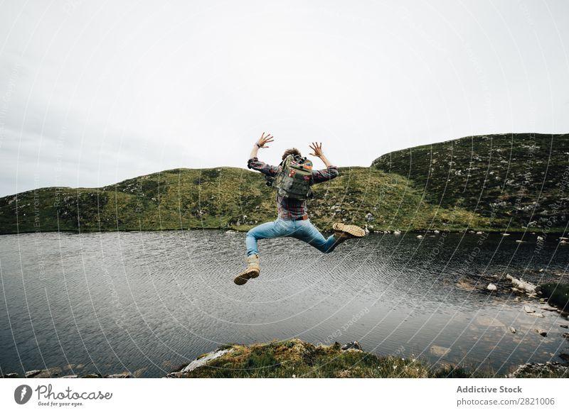 Rucksacktourist springt auf die Landschaft Mann Backpacker springen Freiheit Ferien & Urlaub & Reisen Berge u. Gebirge Fröhlichkeit Seeufer Natur über der Erde