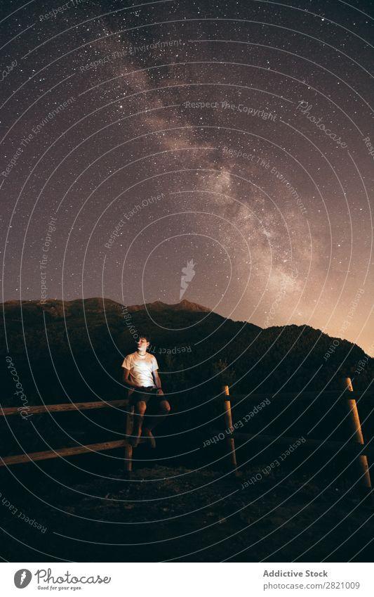Mann sitzt nachts auf dem Zaun. Nacht Stern Holz sitzen Himmel Weltall Licht Galaxie Landschaft dunkel Silhouette Schmuckkörbchen Astronomie Natur sternenklar