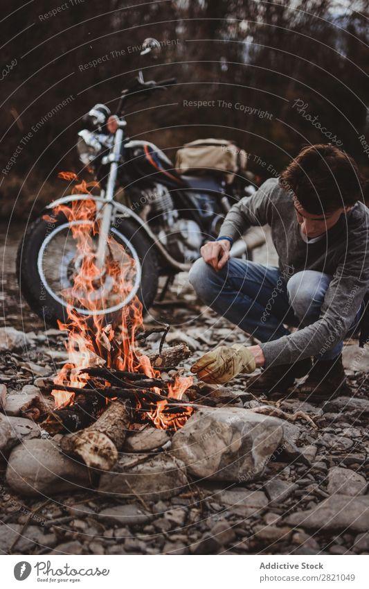 Reisender, der Lagerfeuer hält Mann Feuerstelle Motorrad Einsamkeit Expedition Flamme Brennholz Fernweh Aktion Abenteuer reisend Tourismus wandern Verkehr