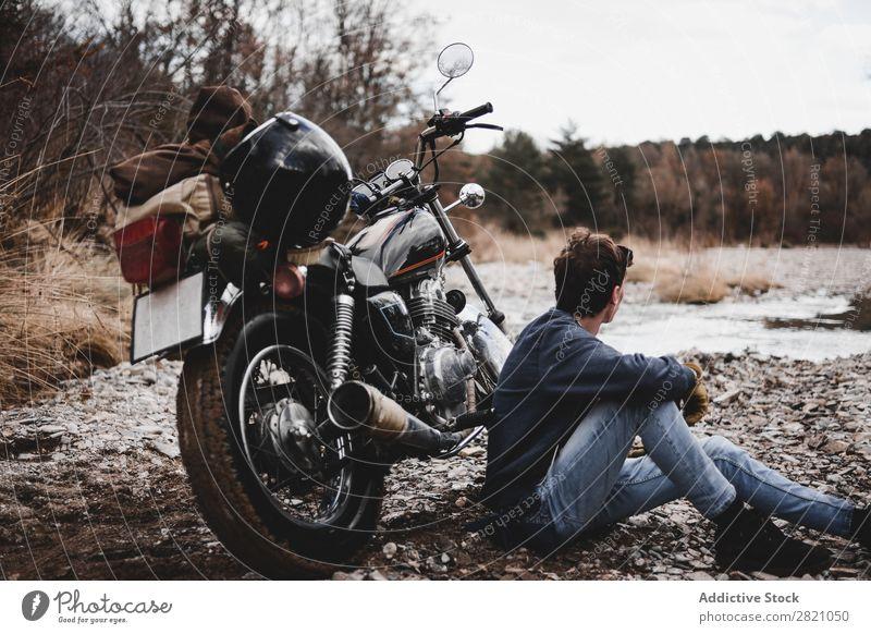Mann sitzt in der Nähe des Motorrads Bach Verkehr Fahrzeug Freiheit Natur Offroad Wasser Fernweh Winter Körperhaltung Reisender selbstbewußt Erkundung