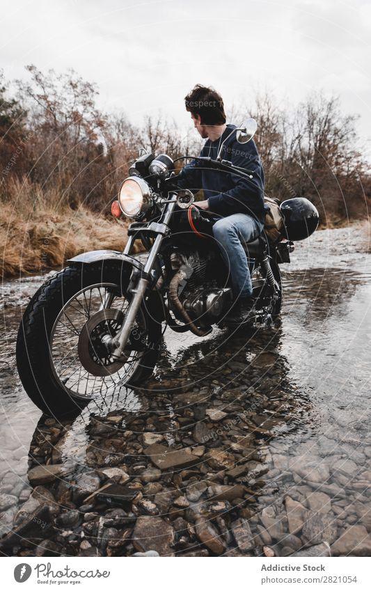 Mann überquert Bach mit dem Motorrad Verkehr Fahrzeug Reiten Freiheit Natur Offroad Wasser Fernweh Schnee Winter Körperhaltung Reisender selbstbewußt Erkundung