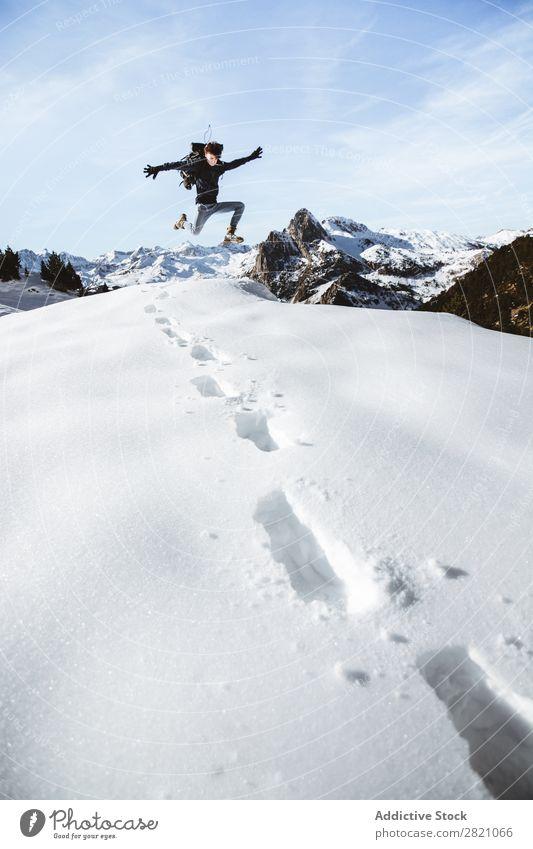 Ein Mann, der in den Schnee springt. Rucksacktourismus Berge u. Gebirge extrem wandern Abenteurer Altimeter