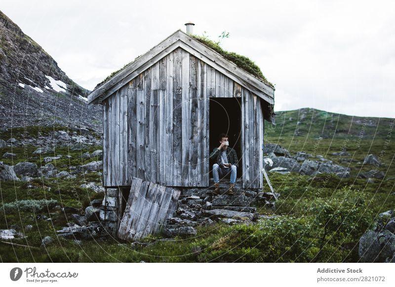 Ein Mann sitzt in einem alten Haus in der Natur. Hütte Berge u. Gebirge abgelegen ruhig Gelände Biegen aber Landschaft friedlich Gebäude Außenseite Idylle