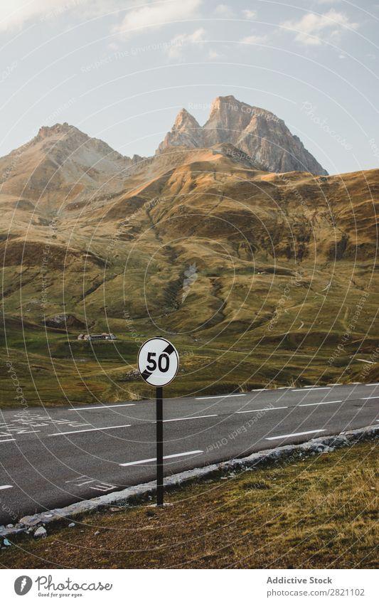 Schild an der Straße in den Bergen Zeichen Geschwindigkeit Asphalt Hügel Berge u. Gebirge Aussicht Sonnenstrahlen Natur Landschaft Ferien & Urlaub & Reisen