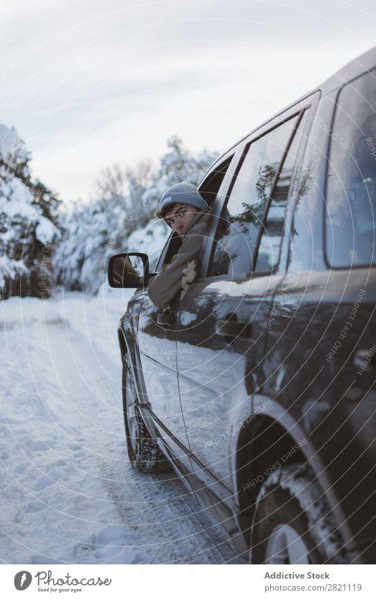 Mann im Auto auf der Winterstraße PKW Straße Wald Mensch Fahrer Schnee