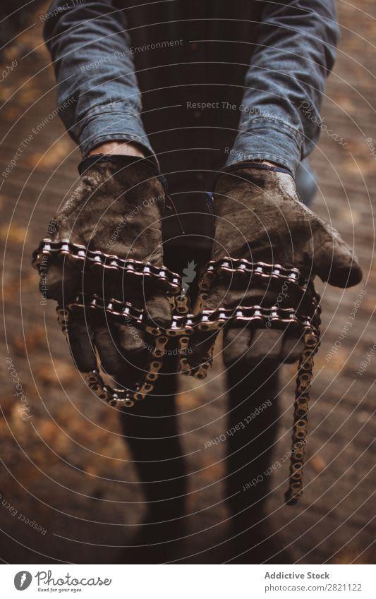 Mann hält Motorradketten fest Handschuhe Arbeitsbekleidung Eisenkette dreckig Gerät abwehrend Schutz Sicherheit Mitarbeiter Industrie Bekleidung