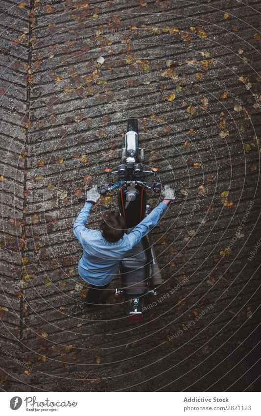 Mann schiebt Motorrad drücken schieben Kraft Verkehr Fahrzeug Fahrrad Gerät Mensch Lokomotive Ausritt Maschine Straße Stil altehrwürdig Ausfall Herbst Blatt