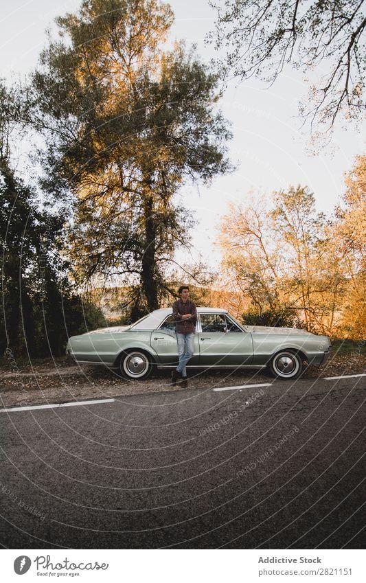 Selbstbewusster Mann, der sich auf den Kofferraum lehnt. PKW Straßenrand anlehnen Rüssel Ferien & Urlaub & Reisen Verkehr