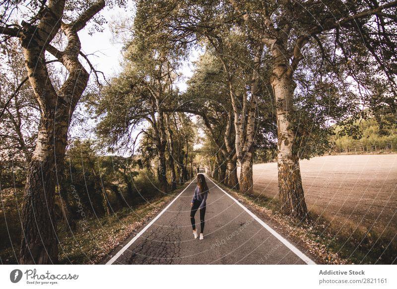 Frau, die auf der Landstraße geht. Straße Feld Ferien & Urlaub & Reisen Landschaft Frischluft Geröll retro Gras regenarm Natur Weg Wege & Pfade Autobahn schön