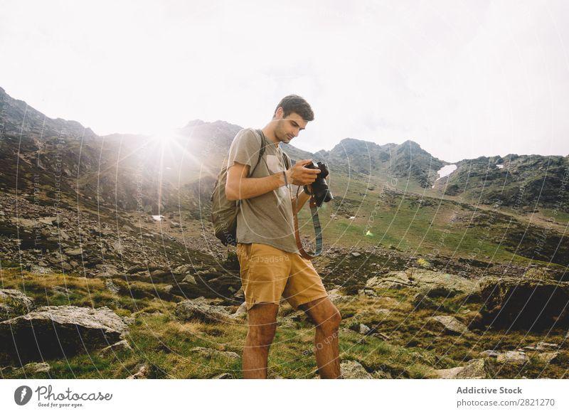 Mann beim Durchsuchen der Kamera in den Bergen Fotograf Berge u. Gebirge Fotokamera Browsen Natur Landschaft Fotografie wandern Tourist Ferien & Urlaub & Reisen