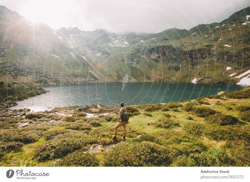 Mann Tourist mit Blick auf den See Hügel Tal Rucksack Horizont Abenteuer Felsen