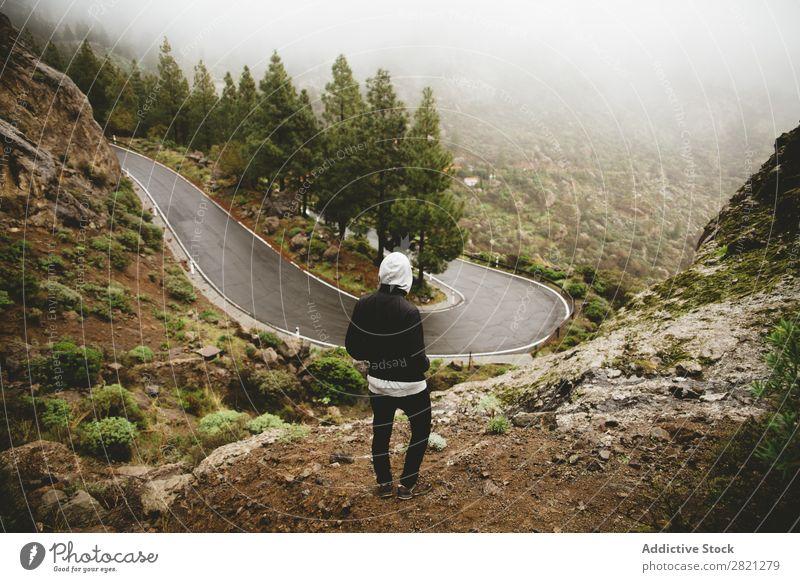 Mann schaut auf Bergstraße Straße Berge u. Gebirge Hügel stehen Abenteuer Natur Ferien & Urlaub & Reisen