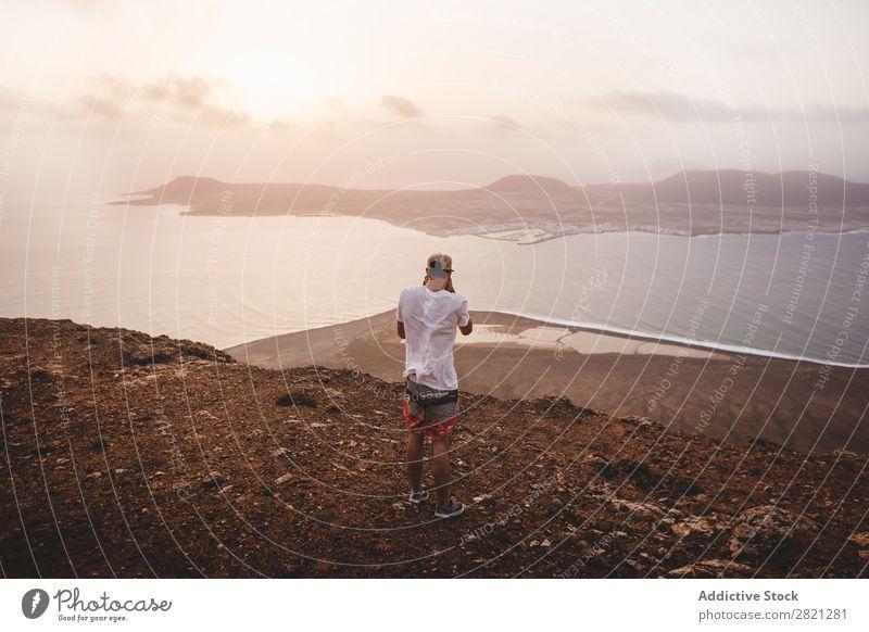 Mann beim Fotografieren der Insel Schießen Klippe Meer Aussicht Landschaft Wasser Küste Ferien & Urlaub & Reisen Natur Meereslandschaft Sommer Himmel Felsen