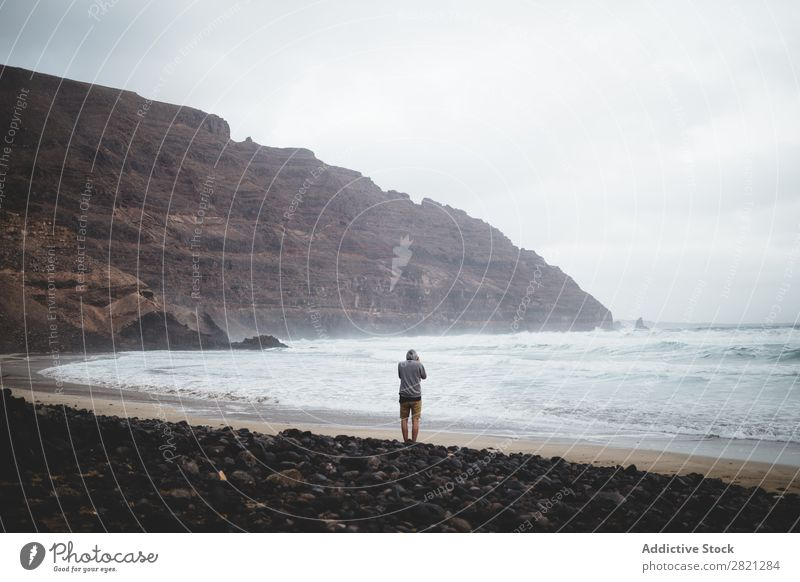Mann, der an einem Strand posiert. Klippe Meer Aussicht Möwe Wellen Landschaft Wasser