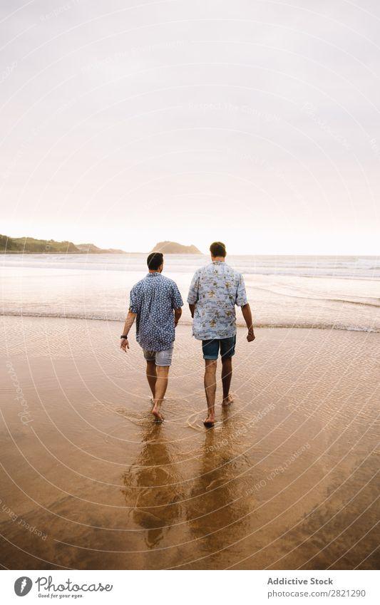 Männer, die zum Meer gehen. Mann laufen Strand Zusammensein Freundschaft Paar Homosexualität Wasser Sand Ferien & Urlaub & Reisen Jugendliche alternativ Natur