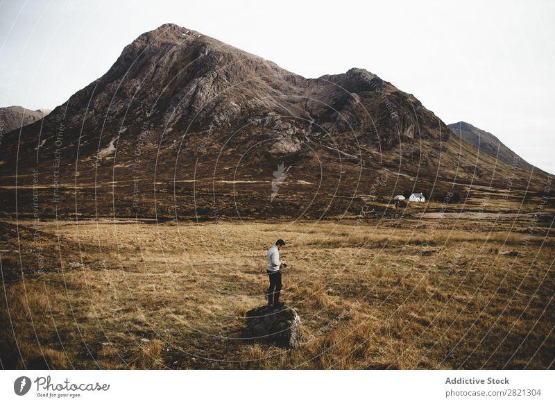 Mann, der auf Felsen im Gebirge posiert. Berge u. Gebirge ländlich Aktion Abenteuer Ferien & Urlaub & Reisen Ebene wandern