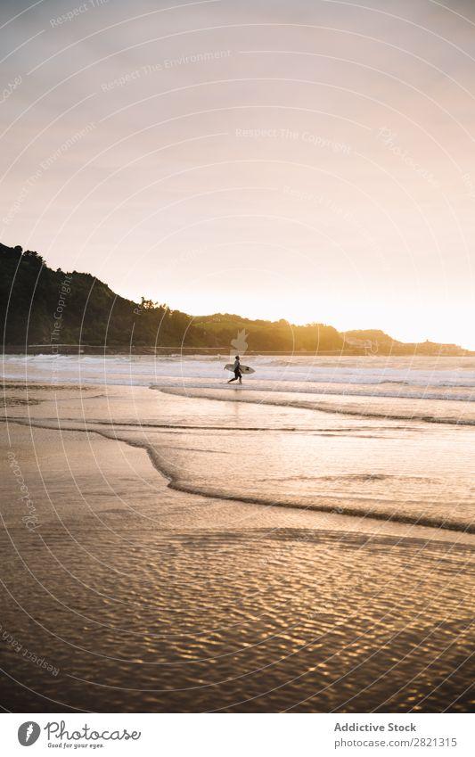 Anonymer Surfer mit Board im Wasser Mensch Strand Abenteuer Sport Küste Sonnenuntergang Urwald Holzplatte Aktion in Bewegung Meer Ferien & Urlaub & Reisen