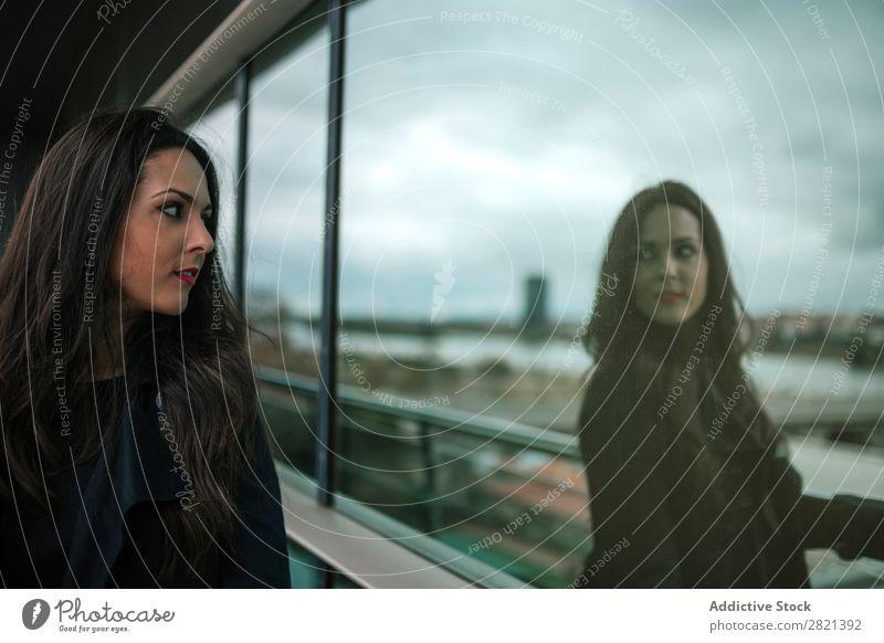 Frau, die auf die Reflexion im Fenster schaut. hübsch Jugendliche schön stehen Reflexion & Spiegelung Gebäude Balkon Großstadt Stadt brünett attraktiv Mensch