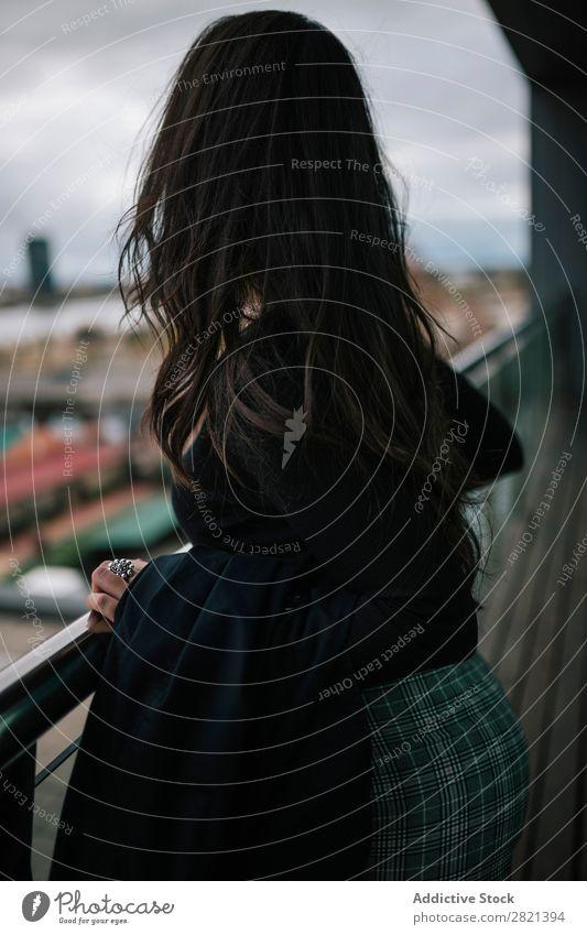 Fröhliche Frau am Handlauf stehend hübsch Jugendliche schön heiter Balkon Gebäude modern Zeitgenosse brünett attraktiv Mensch Beautyfotografie Erwachsene Stil