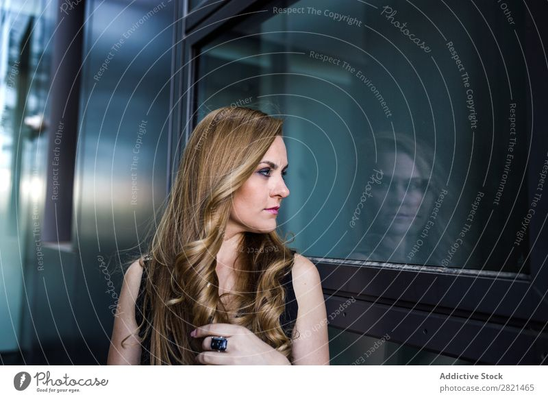 Kaukasische junge Frau betrachtet ihr Spiegelbild in einem Gebäude. Verabredung attraktiv schön blond Kaukasier Feste & Feiern Datierung Kleid elegant Behaarung