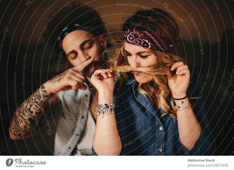 Ein Paar macht einen Schnurrbart mit Haaren und Fingern. Freude Behaarung Wind Spaß haben Porträt Haare & Frisuren Tattoo Lächeln hübsch schön attraktiv Blick