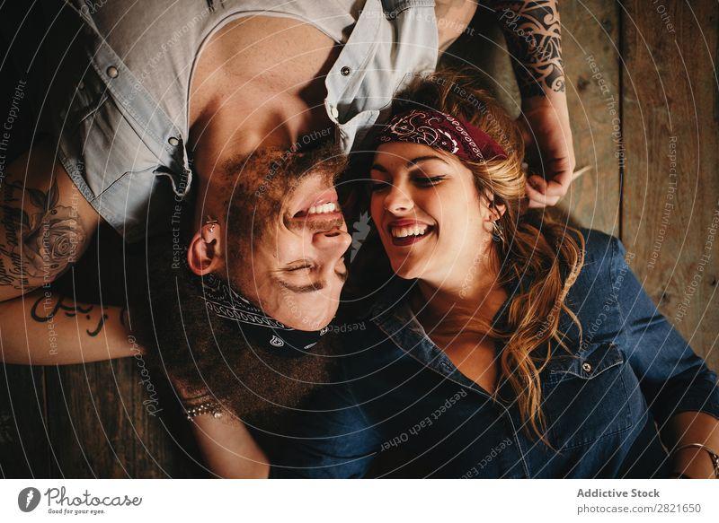 Glückliches Paar auf Holzuntergrund Porträt oben Hintergrundbild lügen Vogelperspektive Lächeln Fröhlichkeit heiter Stirnband Band Stil lachen Augen geschlossen