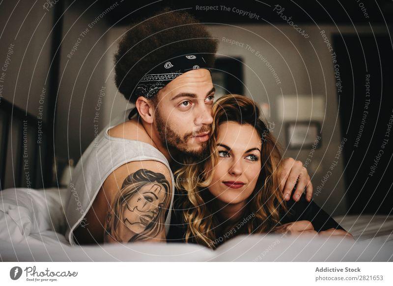Junges Paar umarmt sich auf dem Bett und schaut weg. Schlafzimmer Lächeln Umarmen Angebot Haare & Frisuren lügen Erholung heimwärts Innenaufnahme Zusammensein