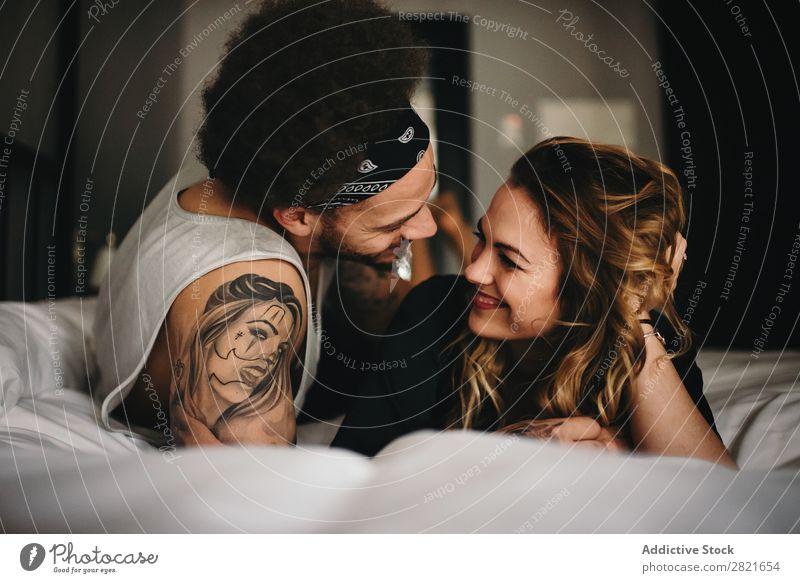 Lächelndes Paar auf dem Bett, das von Angesicht zu Angesicht aussieht. Schlafzimmer Angebot Haare & Frisuren lügen Erholung heimwärts Innenaufnahme Zusammensein