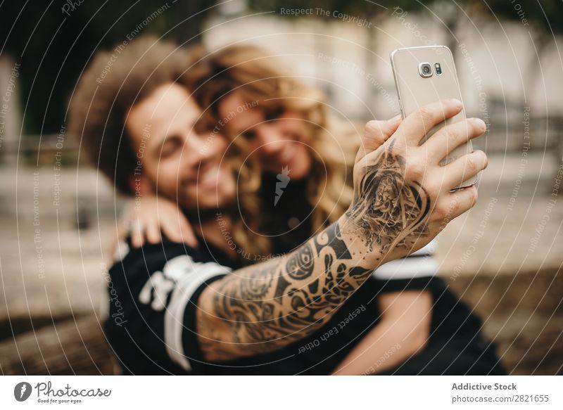 Paarweise Selfie über Smartphone herstellen PDA benutzend Technik & Technologie Fokus Lächeln Umarmen sitzen Außenaufnahme Arme Hand Tattoo alternativ