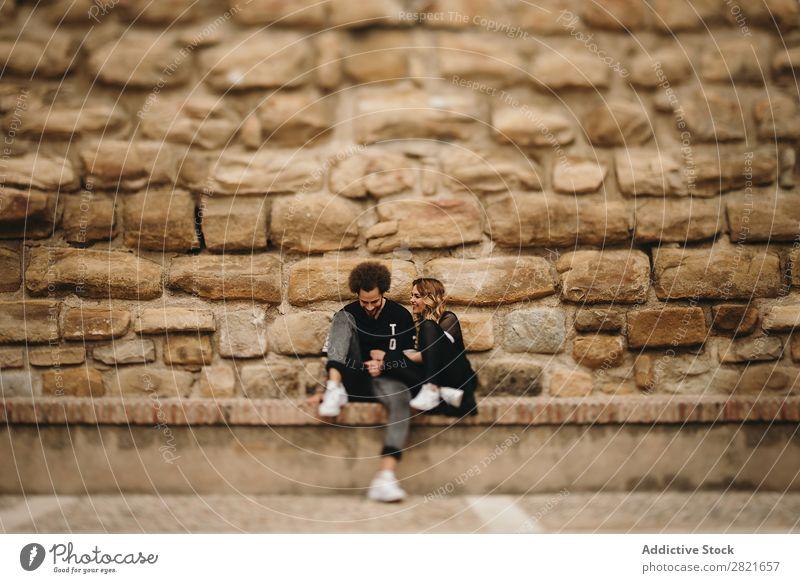 Lächelndes Paar auf Steinhintergrund Porträt Textfreiraum Hintergrundbild Wand sitzen Bank Außenaufnahme Tag Schickimicki Liebe Partnerschaft Angebot blond