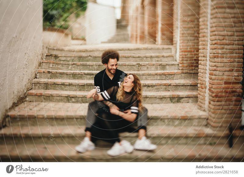 Ein Paar lacht, während es sich an den Stufen in der Stadt umarmt. lachen Spaß haben Porträt Straße sitzen Zusammensein Umarmen Freitreppe ländlich Treppe