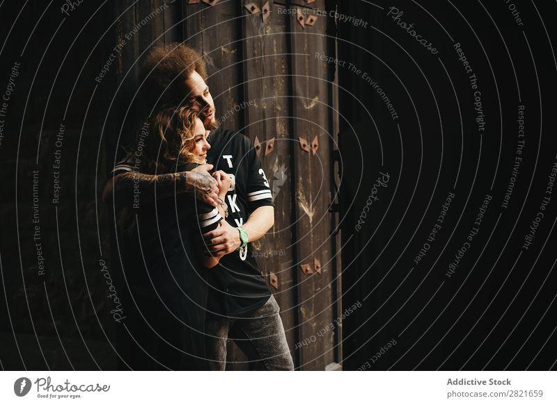Umarmendes Paar, das auf Holzhintergrund wegblickt. Profil Tür Textfreiraum Innenaufnahme offen Wegsehen Haare & Frisuren Tattoo Tag Hintergrundbild Lächeln