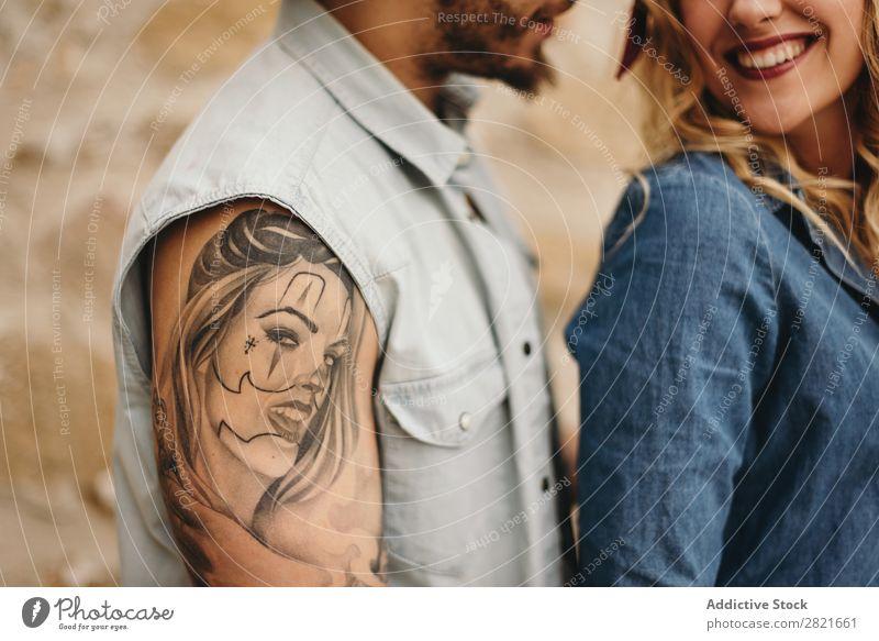 Koppeln Sie sich in Nahaufnahme. Mann mit Tattoo auf dem Gesicht seiner Freundin Paar Lächeln Porträt Mädchen unkenntlich Körperteil Arme Schulter lässig