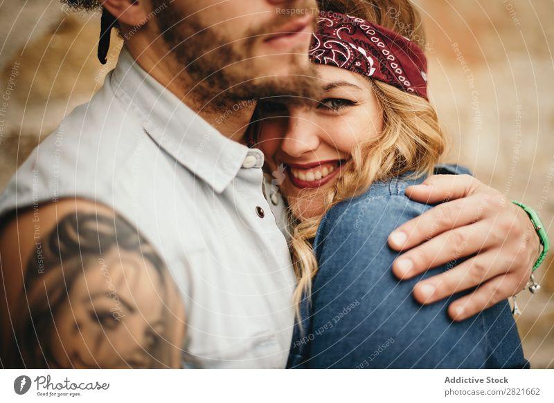 hübsche Freundin mit Band auf dem Kopf in der Umarmung von Freunden Paar Lächeln Nahaufnahme Blick in die Kamera Umarmen Hand Fokus Tattoo Porträt Gesicht