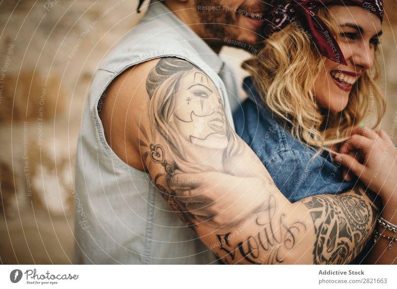 Freund, der seine lächelnde Freundin umarmt. Paar Lächeln Tattoo Arme Umarmen Profil Zahnfarbenes Lächeln Glück schön Gesicht Mädchen Nahaufnahme Körperteil