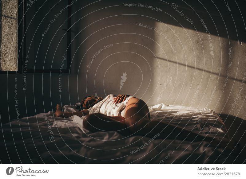 Sinnliche Frau, die im Sonnenlicht auf dem Bett liegt. lügen schlafen Textfreiraum Hintergrundbild itim Intimität Wand Haut Bräune unkenntlich genießen Erotik