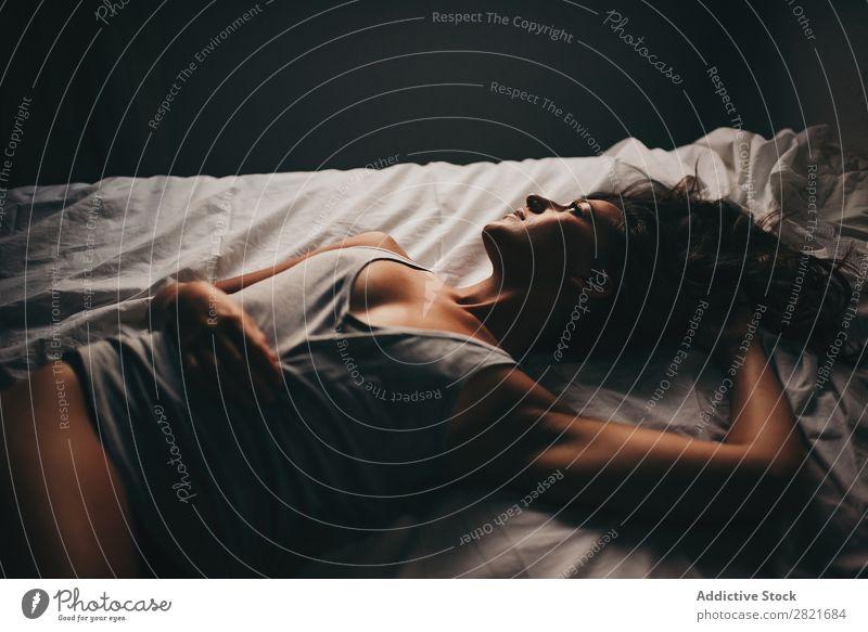 Schöne Frau in grauem Top auf weißem Bett liegend oben Wegsehen Porträt Vogelperspektive Brustansatz Arme Behaarung lügen genießen Erotik Erholung Morgen