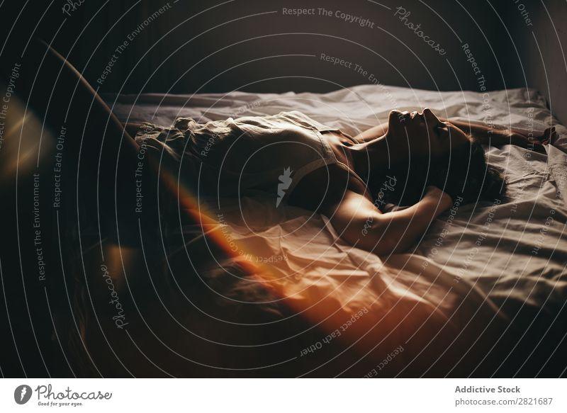Sinnliche Frau im Oberteil auf dem Bett liegend mit geschlossenen Augen und aufgerichteten Armen. Erotik Profil lügen offene Lippen Sex Sonnenlicht blenden itim