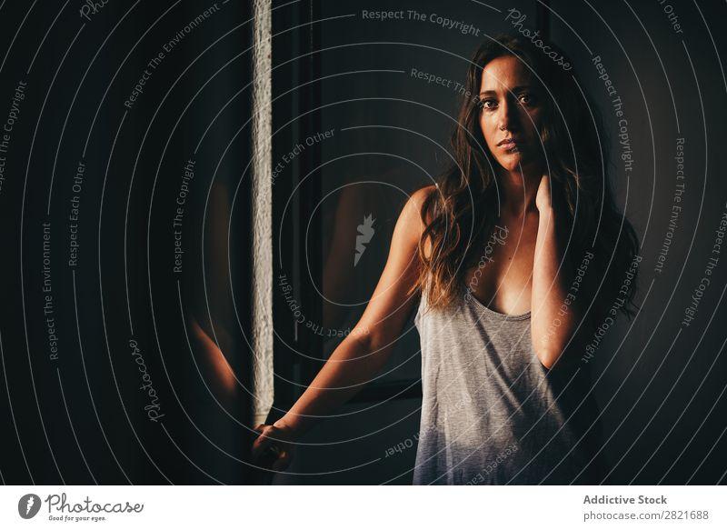 Schöne Frau in Grau mit Hand am Hals am Fenster Körper Körperhaltung Model Blick in die Kamera Arme genießen schön hübsch attraktiv stehen Top Brustwarzen grau