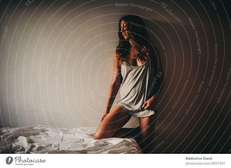 schlanke Frau in grau posierend an der Wand mit Knie auf dem Bett Porträt herabsehend stehen Hintergrundbild Top Brustansatz Bräune dünn Beine Bettwäsche