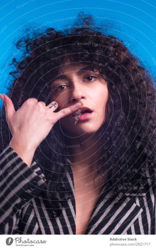 Lockige Frau, die im Studio posiert. hübsch Porträt Jugendliche lockig Behaarung brünett Blick in die Kamera schön Erwachsene Körperhaltung Beautyfotografie