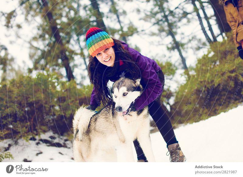 Lachende Frau beim Spielen mit dem Hund im Schnee Boxsport Spaß haben Zusammensein Haustier Säugetier weiß Natur heiter Freude Zufriedenheit kämpfen beißen