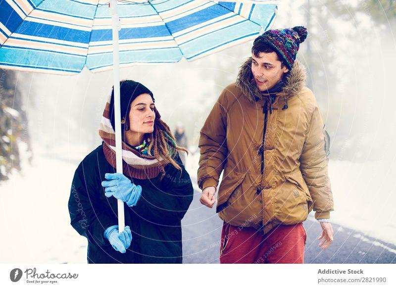 Ein Paar, das auf einer Straße im Wald spazieren geht. Freundschaft Entertainment Freizeit & Hobby Aktion Winter Schnee Natur Außenaufnahme